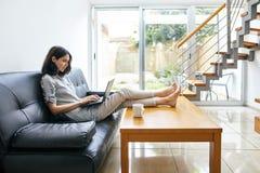 Όμορφη δακτυλογράφηση γυναικών στο lap-top στο σύγχρονο άνετο σπίτι Στοκ Φωτογραφία