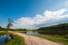 Όμορφη ακόμα λίμνη με τα δέντρα στον ορίζοντα και τα άσπρα αυξομειούμενα σύννεφα στον ουρανό Ειρηνική θερινή ημέρα στο εξοχικό σπ στοκ εικόνα