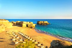 Όμορφη αμμώδης παραλία μεταξύ των βράχων και των απότομων βράχων με τα sunbeds κοντά σε Albufeira στο Αλγκάρβε στοκ φωτογραφία