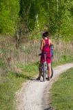 Όμορφη ανακύκλωση κοριτσιών στην άγρια φύση στο βρώμικο δρόμο Ποδήλατα που ανακυκλώνουν το κορίτσι Το κορίτσι οδηγά το ποδήλατο Στοκ φωτογραφία με δικαίωμα ελεύθερης χρήσης