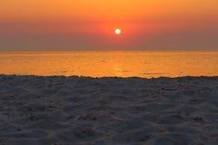 Όμορφη ανατολή στη θάλασσα με τη χρυσή αντανάκλαση στο νερό και το άσπρο πρώτο πλάνο άμμου Στοκ Εικόνα