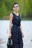 Όμορφη αναδρομική γυναίκα στα εκλεκτής ποιότητας ενδύματα στη λίμνη Στοκ Εικόνα