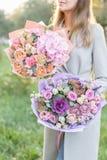 Όμορφη ανθοδέσμη άνοιξη δύο Νέο κορίτσι που κρατά τις ρυθμίσεις λουλουδιών με διάφορο των χρωμάτων Φωτεινό αυγή ή ηλιοβασίλεμα στοκ φωτογραφία με δικαίωμα ελεύθερης χρήσης