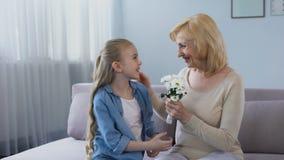 Όμορφη ανθοδέσμη διακοπών μικρών κοριτσιών gifting των chamomiles στο grandma της, προσοχή φιλμ μικρού μήκους