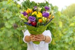 Όμορφη ανθοδέσμη των φρέσκων λαχανικών και των λουλουδιών στα χέρια μιας γυναίκας ως δώρο Στοκ Φωτογραφίες