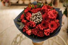 Όμορφη ανθοδέσμη των κόκκινων λουλουδιών με το μαύρο έγγραφο στα χέρια Στοκ Εικόνες