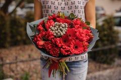 Όμορφη ανθοδέσμη των κόκκινων λουλουδιών με το μαύρο έγγραφο στα χέρια Στοκ εικόνες με δικαίωμα ελεύθερης χρήσης