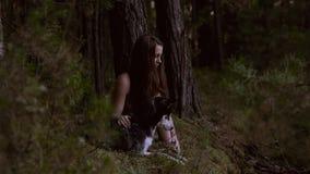 Όμορφη ανοιχτόχρωμης επιδερμίδας νέα γυναίκα και το γεροδεμένο σκυλί της που κοιτάζουν κάτω από από κοινού απόθεμα βίντεο