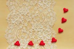 Όμορφη δαντέλλα σε χαρτί με τις κόκκινες καρδιές Στοκ Εικόνες