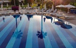 Όμορφη αντανάκλαση στο σαφές νερό της μπλε πισίνας με το μόνιππο -μόνιππο-longues στο ξενοδοχείο θερέτρου πολυτέλειας Στοκ φωτογραφία με δικαίωμα ελεύθερης χρήσης