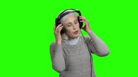 Όμορφη ανώτερη γυναίκα που ακούει τη μουσική στα ακουστικά απόθεμα βίντεο