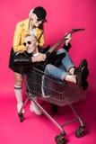 Όμορφη ανώτερη γυναίκα που κλίνει στο καροτσάκι αγορών με τον ανώτερο άνδρα που παίζει την ηλεκτρική κιθάρα Στοκ Εικόνες
