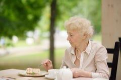 Όμορφη ανώτερη κυρία με το σγουρό άσπρο τσάι κατανάλωσης τρίχας υπαίθρια στον καφέ ή το εστιατόριο Στοκ Εικόνες