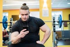 Όμορφη αποστολή κειμενικών μηνυμάτων τύπων στο smartphone του στη γυμναστική Στοκ Φωτογραφία