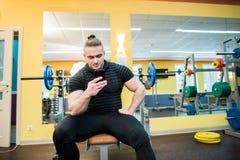 Όμορφη αποστολή κειμενικών μηνυμάτων τύπων στο smartphone του στη γυμναστική Στοκ Φωτογραφίες