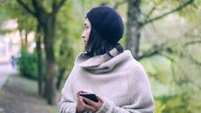 Όμορφη ασιατική γυναίκα με ένα smartphone σε ένα πάρκο φθινοπώρου απόθεμα βίντεο