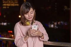 Όμορφη ασιατική γυναίκα με το έξυπνο τηλέφωνο και τα κίτρινα ακουστικά στοκ φωτογραφία με δικαίωμα ελεύθερης χρήσης