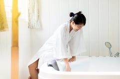 Όμορφη ασιατική γυναίκα που γεμίζει επάνω με το νερό και που χαλαρώνει στην μπανιέρα στη SPA στοκ εικόνες
