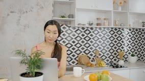 Όμορφη ασιατική γυναίκα που εργάζεται μακρινά στο lap-top στην κουζίνα απόθεμα βίντεο
