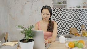 Όμορφη ασιατική γυναίκα που εργάζεται στο lap-top της στην εγχώρια κουζίνα με τα φρούτα απόθεμα βίντεο