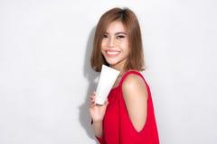 Όμορφη ασιατική γυναίκα που στέκεται το κόκκινο φόρεμα και που κρατά τις καλλυντικές δημόσιες σχέσεις Στοκ Εικόνες