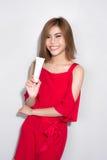 Όμορφη ασιατική γυναίκα που στέκεται το κόκκινο φόρεμα και που κρατά τις καλλυντικές δημόσιες σχέσεις Στοκ Φωτογραφία