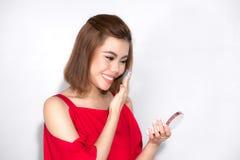 Όμορφη ασιατική γυναίκα που στέκεται το κόκκινο φόρεμα και που κρατά τις καλλυντικές δημόσιες σχέσεις Στοκ εικόνες με δικαίωμα ελεύθερης χρήσης