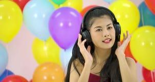 Όμορφη ασιατική γυναίκα που χορεύει με το ζωηρόχρωμο υπόβαθρο μπαλονιών στο κόμμα σε σε αργή κίνηση απόθεμα βίντεο