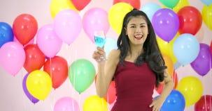 Όμορφη ασιατική γυναίκα που χορεύει με το ζωηρόχρωμο υπόβαθρο μπαλονιών στο κόμμα σε σε αργή κίνηση φιλμ μικρού μήκους