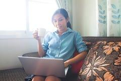 Όμορφη ασιατική γυναίκα που χρησιμοποιεί τα κοινωνικά μέσα, Διαδίκτυο στο lap-top r στοκ φωτογραφία