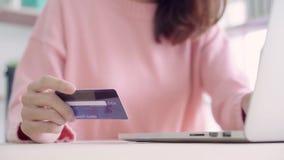 Όμορφη ασιατική γυναίκα που χρησιμοποιεί τον υπολογιστή ή lap-top που αγοράζει on-line να ψωνίσει από την πιστωτική κάρτα ενώ συν απόθεμα βίντεο
