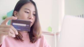 Όμορφη ασιατική γυναίκα που χρησιμοποιεί τον υπολογιστή ή lap-top που αγοράζει on-line να ψωνίσει από την πιστωτική κάρτα απόθεμα βίντεο