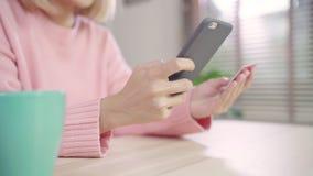 Όμορφη ασιατική γυναίκα που χρησιμοποιεί το smartphone που αγοράζει on-line να ψωνίσει από την πιστωτική κάρτα ενώ συνεδρίαση που απόθεμα βίντεο