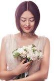 Όμορφη ασιατική γυναίκα στο άσπρο φόρεμα με την ανθοδέσμη των λουλουδιών στα χέρια Στοκ Εικόνες
