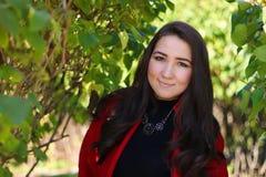 Όμορφη ασιατική γυναίκα στο κόκκινο παλτό στοκ φωτογραφίες