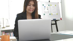 Όμορφη ασιατική επιχειρησιακή γυναίκα που εργάζεται με το φορητό προσωπικό υπολογιστή στο σύγχρονο γραφείο απόθεμα βίντεο