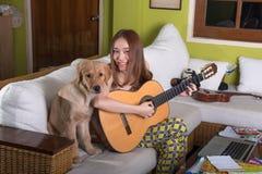 Όμορφη ασιατική κιθάρα παιχνιδιού κοριτσιών ευτυχώς με το σκυλί Στοκ φωτογραφία με δικαίωμα ελεύθερης χρήσης