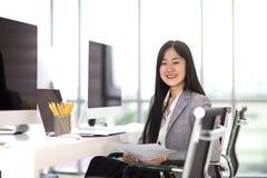 Όμορφη ασιατική συνεδρίαση επιχειρησιακών γυναικών και χαμόγελο στην καρέκλα στο μ στοκ εικόνα με δικαίωμα ελεύθερης χρήσης