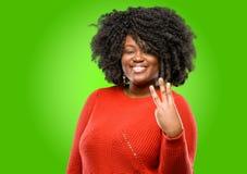 Όμορφη αφρικανική γυναίκα με τη σγουρή τρίχα που απομονώνεται πέρα από το πράσινο υπόβαθρο στοκ εικόνες