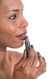 Όμορφη αφρικανική γυναίκα που εφαρμόζει το κόκκινο κραγιόν, πυροβολισμός κινηματογραφήσεων σε πρώτο πλάνο Στοκ εικόνα με δικαίωμα ελεύθερης χρήσης