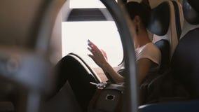 Όμορφη βέβαια καυκάσια γυναίκα που χρησιμοποιεί τον αγγελιοφόρο app στο ταξίδι smartphone και χαμόγελου στο κάθισμα παραθύρων τρα φιλμ μικρού μήκους