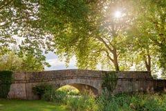 Όμορφη γέφυρα πετρών πέρα από μια μικρή λίμνη με τα δέντρα πίσω στο α Στοκ εικόνες με δικαίωμα ελεύθερης χρήσης