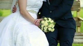 Όμορφη γαμήλια ανθοδέσμη στα χέρια της νύφης και του νεόνυμφου απόθεμα βίντεο