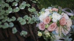 Όμορφη γαμήλια ανθοδέσμη των άσπρων τριαντάφυλλων και creme των γαρίφαλων στη χλόη κοντά σε ένα δρύινο δέντρο Ανθοδέσμη διαφορετι απόθεμα βίντεο