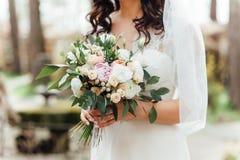Όμορφη γαμήλια ανθοδέσμη στα χέρια της νύφης Στοκ Εικόνα
