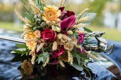 Όμορφη γαμήλια ανθοδέσμη στην κουκούλα αυτοκινήτων Στοκ Εικόνες
