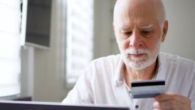 Όμορφη γενειοφόρος ανώτερη συνεδρίαση ατόμων στο σπίτι Να ψωνίσει on-line με την πιστωτική κάρτα στο lap-top φιλμ μικρού μήκους