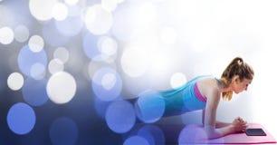 Όμορφη γιόγκα άσκησης γυναικών με την ψηφιακή ταμπλέτα στη μετάβαση bokeh στοκ φωτογραφία