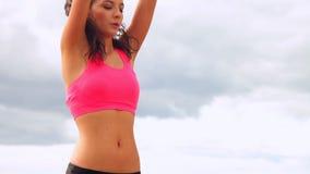 Όμορφη γιόγκα άσκησης brunette στην παραλία φιλμ μικρού μήκους