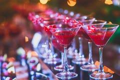 Όμορφη γραμμή διαφορετικών χρωματισμένων κοκτέιλ οινοπνεύματος με τον καπνό σε μια γιορτή Χριστουγέννων, ένα tequila, martini, μι Στοκ Φωτογραφίες